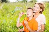 Happy mother and son in the park blowing soap bubbles outdoor portrait