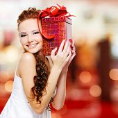 stock photo of birthday  - Happy young woman with birthday present in hands posing indoors - JPG