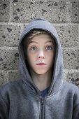 Portrait Of A Male Teenager With Wide Eyed In Front Of A Wall