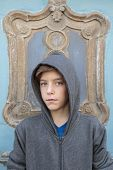Portrait Of A Male Teenager With Gray Hoody In Front Of A Ornamental Door