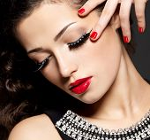 Fashion woman with modern creative makeup using false eyelashes red manicure