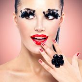 Face of beautiful fashion woman with red sexy lips and  black false eyelashes at studio