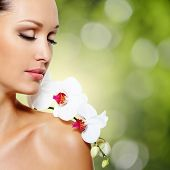 Beauty face of  beautiful woman with a white orchid flower. Skin care treatment. Green nature backgr