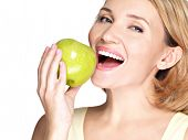 Beautiful young woman biting the biting a fresh ripe apple - on white background.