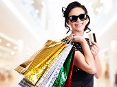 Happy woman in sunglasses with purchasing and credit card in the shop.