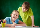 Portrait of cute schoolgirl looking at camera while drawing at lesson with her classmate standing ne