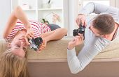 Young couple laying on the bed with heads upside down and taking pictures with old analog SLR camera