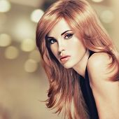 Portrait of a beautiful woman with long straight red hair. Fashion model instagram styling