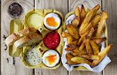 Two Soft Boiled Eggs With Fries And Sauces.