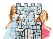 picture of fancy-dress  - Two little girls play to be princess and standing behind castle tower made of cardboard wearing costume dress and smiling - JPG