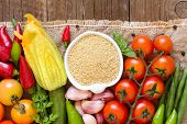 image of millet  - Raw Organic millet in bowl and vegetables on the wooden table  - JPG