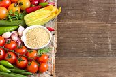 picture of millet  - Raw Organic millet in bowl and vegetables on the wooden table - JPG