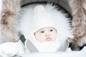 Funny Little Baby In A Warm Stroller On A Cold Winter Day