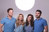 smiling group of casual people looking up into a big ball of light