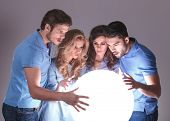 worried group of people reading about their future in a ball of light