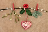 Christmas heart decoration, with holly, fir and mistletoe on a  pussy willow branch over old brown p