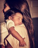 Portrait of mother standing back side and caring little sleeping baby on shoulders, enjoying mild sunset light, happy young family, peace concept