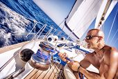 Handsome strong man working on sailboat, sailor enjoys crew duty, luxury holidays, yachting sport ac