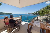 DUBROVNIK, CROATIA - MAY 28, 2014: Couple sitting and admiring stunning view over the Adriatic sea from the terrace of Villa Dubrovnik, one of Dubrovnik's most exclusive hotel and restaurant.