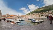 DUBROVNIK, CROATIA - MAY 26, 2014: Small boats in city port with mount Srdj in background. Port is safe haven for many private boats of local citizens.
