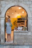 DUBROVNIK, CROATIA - MAY 26, 2014: Saleswoman in store front on Stradun in Dubrovnik, Croatia