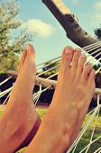 closeup of the bare feet of a man who is relaxing in a hammock
