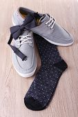 Top-siders, bow-tie and socks on wooden background