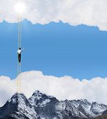 Businessman standing on ladder high above mountain scene