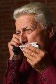 Sick mature man speaking on phone