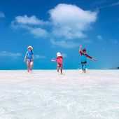 Mother and kids on a Caribbean vacation running at shallow water