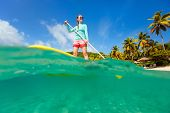 Split underwater photo of young sporty woman on tropical beach vacation paddling on stand up board