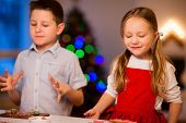 Two kids baking gingerbread cookies at home on Christmas eve