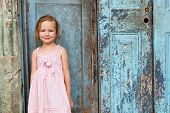 Portrait of adorable little girl outdoors on a street against old door