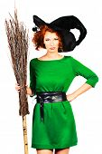 Portrait of a charming red-haired witch with broom. Halloween. Isolated over white.