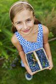 Blueberries -  Lovely girl with picked fresh blueberries in the garden