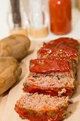 Sliced Meatloaf And Baked Potatoes On Wood Board