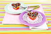 Delicious rainbow mini cakes on plates, on bright background
