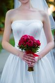 Bride Holding A Wedding Bouquet Of Red Roses.