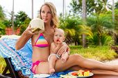 Beautiful Mother And Child In The Open Air. Nature. Beauty Mother And Her Baby Eat The Fruit Togethe