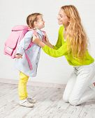 Mother helps her daughter get ready for school. Mom support child to wear a backpack