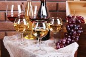 Bottles and glasses of wine and ripe grapes on table on brick wall background