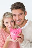 Portrait of attractive young couple holding piggybank over white background