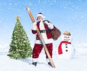 Santa claus holding sack and skis next to a christmas tree.