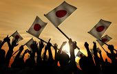 Group of People Waving Japanese Flags in Back Lit