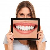 stock photo of human teeth  - Cute woman holding a tablet with her teeth - JPG