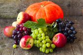 Pumpkin, Apples, Grapes On A Wooden Background