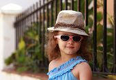 Fashion Kid Girl In Glasses And Hat Outdoors Background. Closeup
