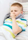 childhood, healthcare and medicine concept - ill boy with flu coughing at home