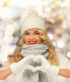 happiness, winter holidays, gesture, charity and people concept - smiling young woman in white hat a