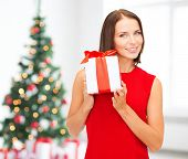 x-mas, holidays, valentine's day, celebration and people concept - smiling woman in red dress with gift box over living room and christmas tree background